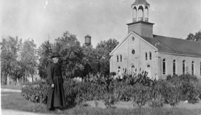 Br. Edward J. McEachen, CSV, groundskeeper from 1906 – 1920, stands in front of Maternity BVM Church in Bourbonnais, IL, the cradle of the Clerics of St. Viator in the United States